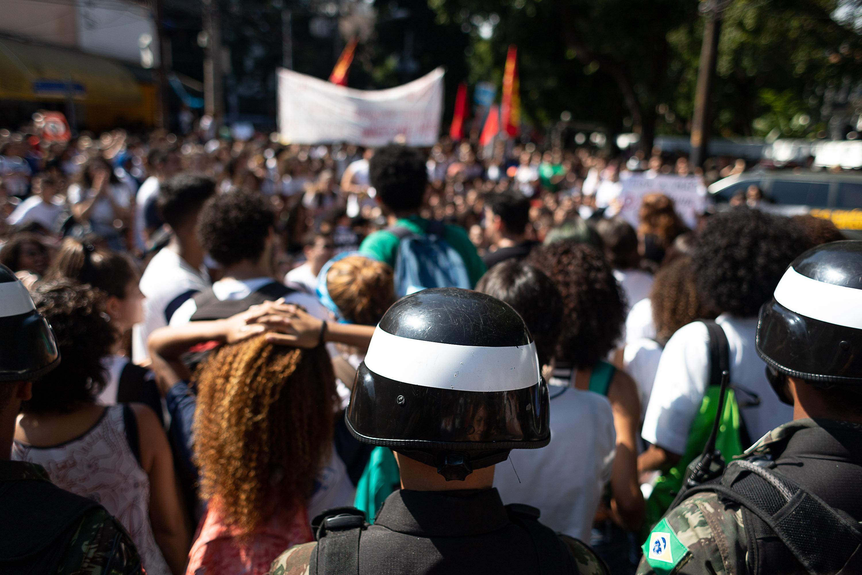 Mãos na cabeça! Governo Bolsonaro faz corte de verbas na educação. Estudantes protestam pacificamente, mas com exército a postos.